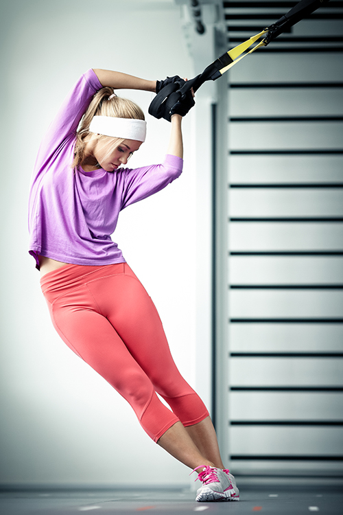 Young woman streching muscles TRX training